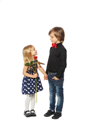 Girl with a rose in her hand standing near the boy on a white background photo