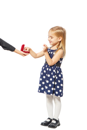 baby open present: Girl takes a ring box that holds the hand of a boy Stock Photo