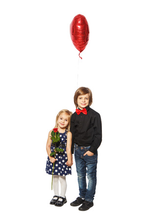 Girl with a rose in her hand standing near the boy with balloon in the form of heart on a white background photo