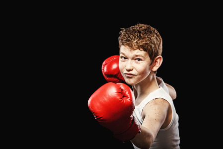 Red-haired boy on a black background with red boxing gloves