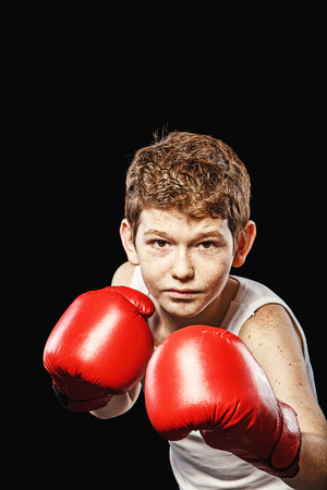 boxing boy: Red-haired boy on a black background with red boxing gloves