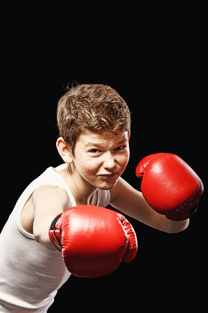 boy boxing: Red-haired boy on a black background with red boxing gloves