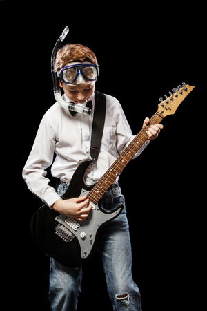 young musician: The red-haired boy in a white shirt with an electric guitar on a black background Stock Photo