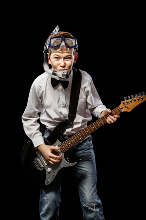 tubes: The red-haired boy in a white shirt with an electric guitar on a black background Stock Photo