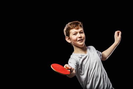 jugando tenis: Mesa Niño jugando tenis en un fondo negro Foto de archivo
