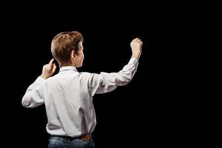 laughable: Red-haired boy standing with his back against a black background and something draws Stock Photo