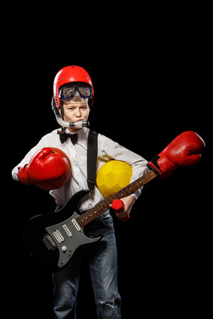 implements: The red-haired boy with a variety of implements on itself on a black background Stock Photo