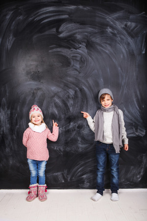 Beautiful boy and girl standing on a gray background. Background is well suited for drawing anything. photo