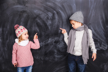 ��beautiful boy�: Beautiful boy and girl standing on a gray background. Background is well suited for drawing anything.