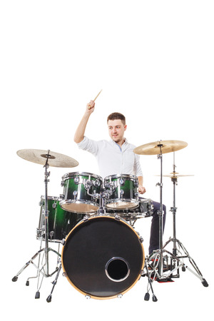 concert background: Handsome guy behind the drum kit on a white background in shirt and trousers