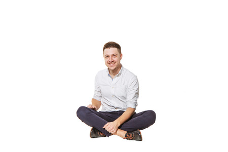 ttractive: Young and handsome guy in shirt and trousers sitting on a white background