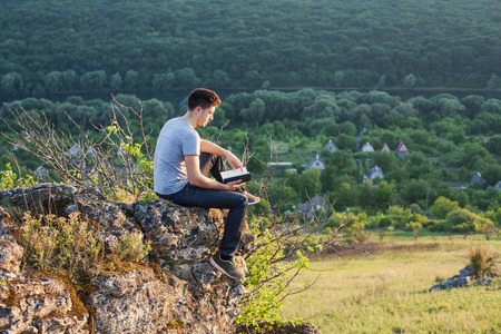 a man sitting on the edge of a cliff and reading a book Фото со стока