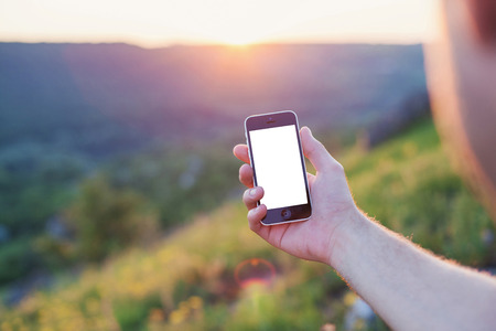 Mens hand hold the phone with the white screen on a background of sunset horizontal