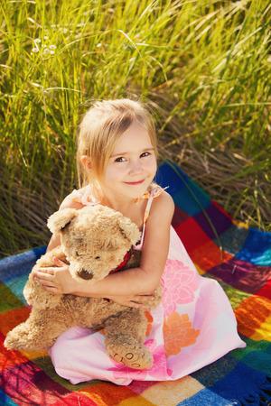 oso de peluche: Ni�a con el oso de peluche en la naturaleza Foto de archivo