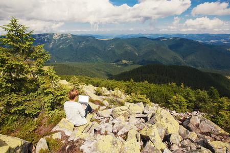 노트북과 언덕에 앉아있는 여자 스톡 콘텐츠