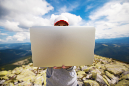 Woman with laptop standing on a stone in the mountain 版權商用圖片