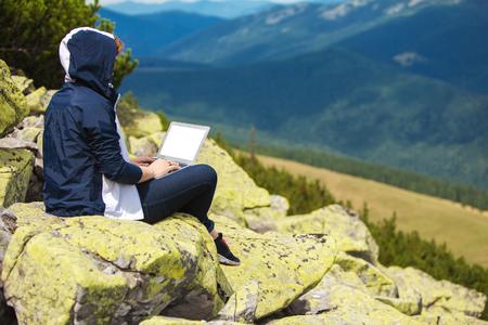 산에서 돌에 앉아 노트북을 가진 여자