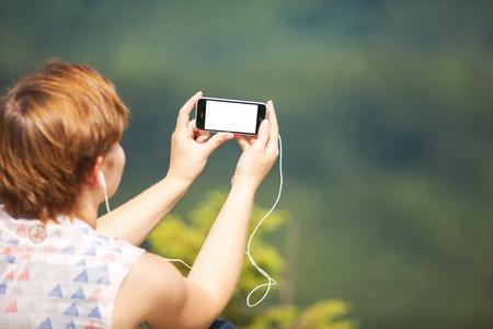 언덕에 앉아서 전화로 음악을 듣는 여자