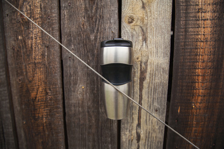 Thermo cup on a wooden fence