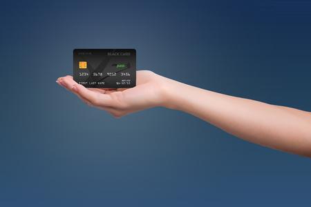 파란색 배경에 여자 손에 검은 신용 카드