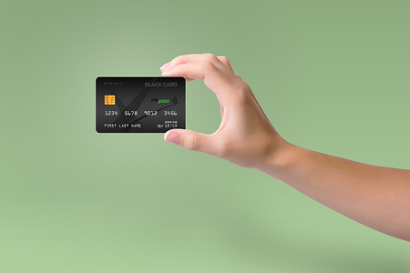 Isolated black credit card in woman hand on green background
