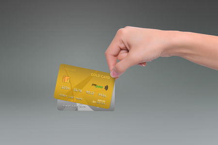 net income: Isolated gold and gray credit cards in woman hand