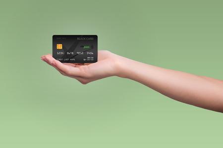 녹색 배경에 여자 손에 고립 된 검은 신용 카드