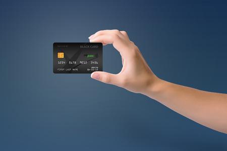 Black credit card in woman hand on blue background 版權商用圖片