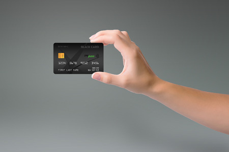 Isolated black credit card in woman hand on gray background 版權商用圖片