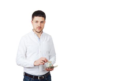 흰 셔츠를 입은 남자가 돈을 센다.