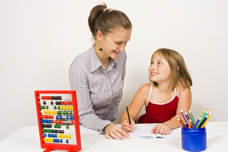 eachother: A young teacher, or mother, and her student, or little daughter, smiling to eachother, studying together against white wall - some educational tools and objects on the table. Stock Photo