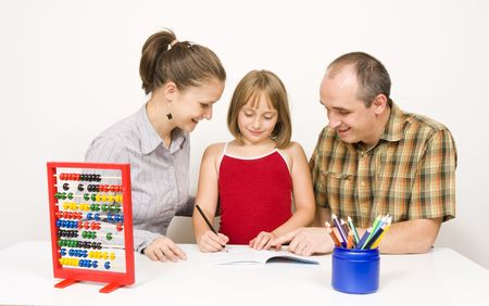 educational tools: A happy family sitting together. the parents are helping their little daughter with the homework against white wall - some educational tools and objects on the table.