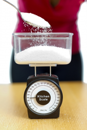 kg: Woman pouring sugar into a kitchen scale. Stock Photo