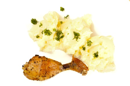 yeloow: Mashed potato with parsley and a fried chicken leg isolated on white.