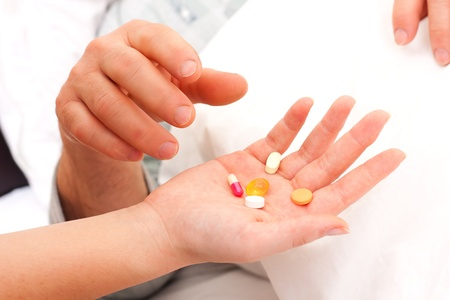 A nurse 's hands givng pills and drugs to a laying senior man. Stock Photo - 17049973
