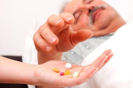drug use: Pills held by nurse, being taken by senior patient.