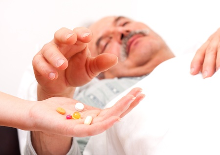 drug use: Pills held by nurse, taken by elderly patient.