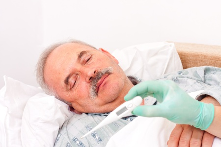 caucasian fever: Elderly man laying in bed, nurse taking temperature. Stock Photo