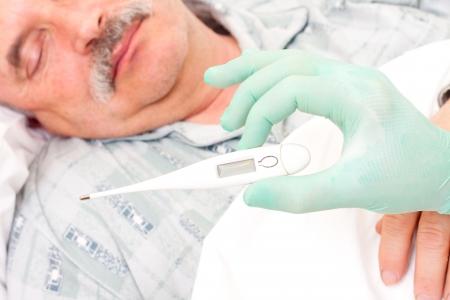 taken: Temperature taken  by nurse of an elderly male patient.