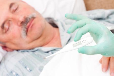 infirm: Temperature taken  by nurse of an elderly male patient.