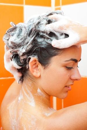 mujer bañandose: Chica morena joven lavándose el pelo largo en la cabina.