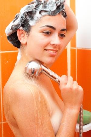 cabine de douche: Jeune fille tenant douche et se laver les cheveux avec un shampooing � long - vue de c�t�.