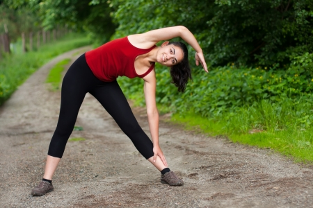 sport clothes: Smiling young girl stretching outdoors. Stock Photo