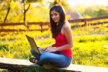 Attractive woman working outdoors on her laptop.
