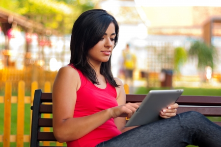 Attractive young woman sitting outdoors reading on touchscreen tablet. Archivio Fotografico
