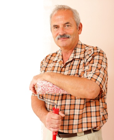 Smiling senior man standing in front of a  half painted wall, holding a paint roller.  photo