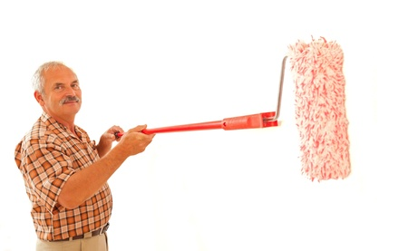 redecorate: Smiling senior man painting white wall with paint roller. Stock Photo