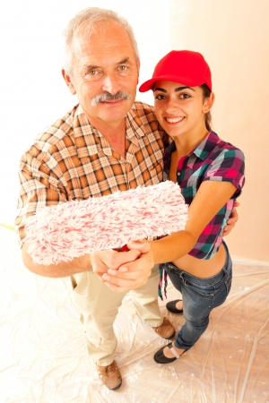 Father and daughter smiling and holding a paint roller. photo