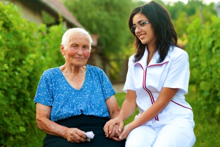 A young doctor  nurse visiting an elderly sick woman holding her hands with caring attitude. photo
