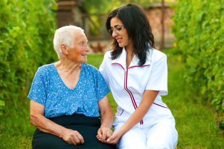 assisting: A young doctor  nurse chatting with an elderly sick woman holding her hands with caring attitude. Stock Photo